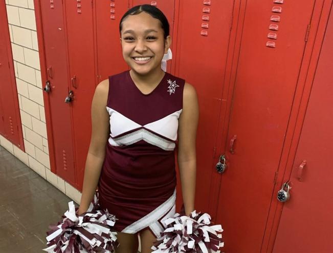 Cheerleader standing in front of lockers