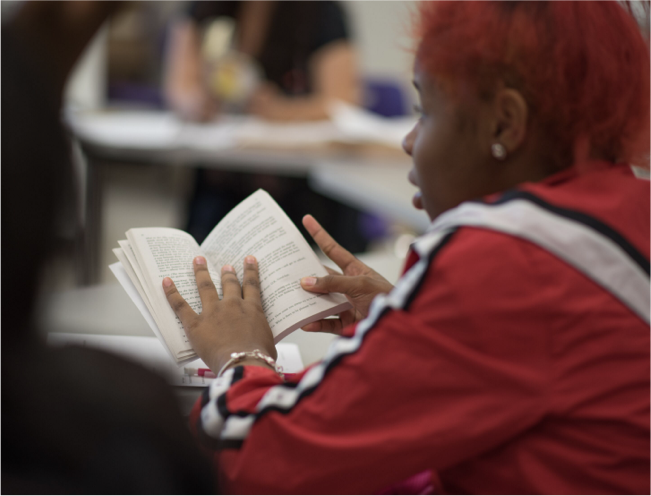 Student in classroom holding book