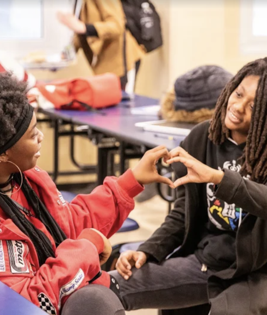 Two students making a heart shape with their hands
