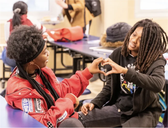 Students forming heart shape with hands