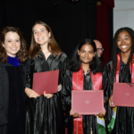 Four students holding diplomas on graduation day