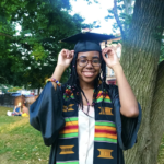 Student smiling under tree on graduation day