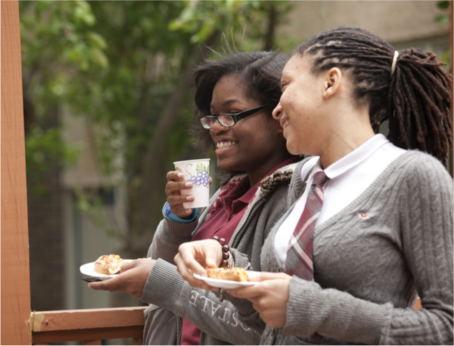 Two students enjoying refreshments in a garden