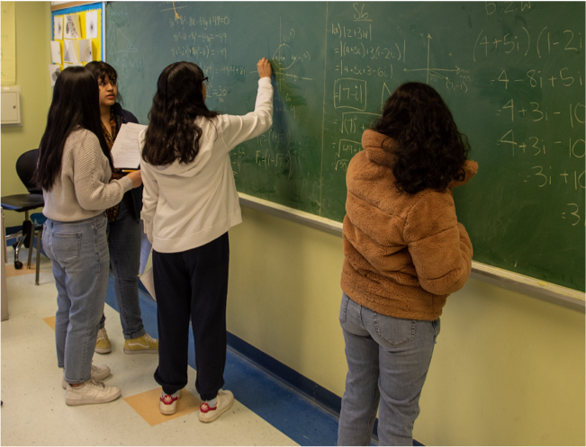 Students solving math problems on the blackboard
