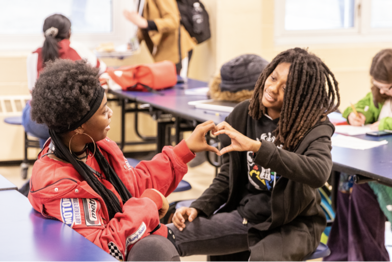 Two students creating a heart shape with hands