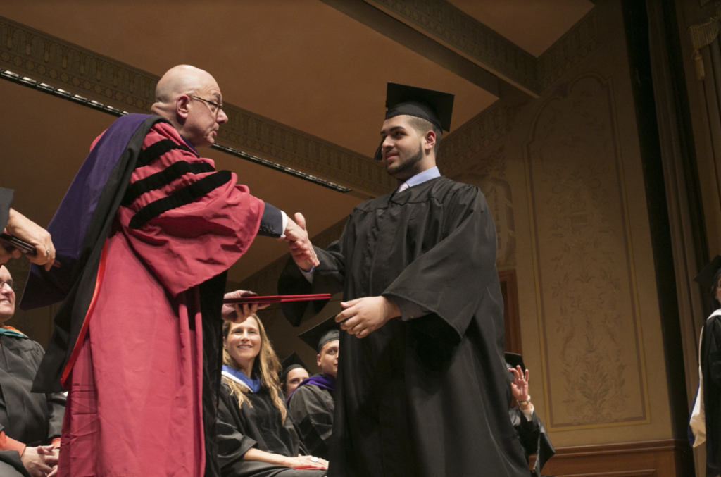 Student receiving diploma on graduation day